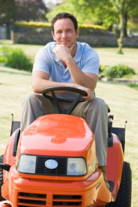 Man sitting on a riding lawn mower. He has a large yard so he likes riding lawn mowers better than push mowers.